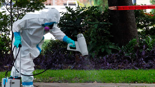 A man dressed in protective hazmat clothing treats the sidewalk in front of an apartment where a second person diagnosed with the Ebola virus resides on October 12, in Dallas, Texas
